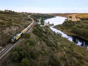 Comboio transporte de mercadorias MEDWAY com o rio à sua direita e árvores a rodeá-lo