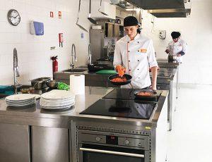 duas pessoas numa cozinha a cozinhar