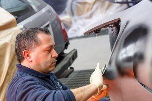 homem com casaco da mercedes a trabalhar num carro